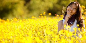 Lady in a field of yellow flowers